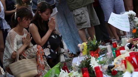 Frauen knien an einem Denkmal einen Tag nachdem ein Van zahlreiche Fußgänger in Las Ramblas in Barcelona tötete und verletzte, Spanien 18. August 2017