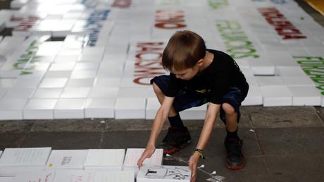 Ein Junge platziert einen Stein während einer Aktion von Amnesty International gegen Trumps Mauer in Mexiko-Stadt, Mexiko, 10. Juni 2017.