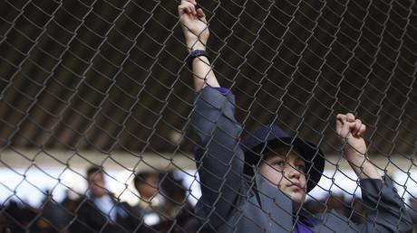 Ein junger Zeuge Jehovas blickt durch einen Zaun (eine große Versammlung der Organisation im Azteca-Stadion, Mexiko-Stadt, Dezember 2013)