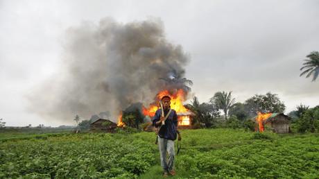 Ein ethnischer Rakhine hält selbstgebaute Waffen in den Händen, und entfernt sich von einem in Flammen stehenden Haus, welches bei Kämpfen zwischen buddhistischen Rakhine und den Rohingya-Muslimen in Brand geriet, Sittwe, Myanmar, 10. Juni 2012.
