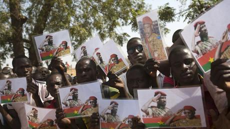 Einwohner von  Ouagadougou zeigen Bilder des ehemaligen Präsidenten Thomas Sankara bei einer Begräbniszeremonie für gefallene Demonstranten während der Protestwelle im Oktober 2014, Burkina Faso