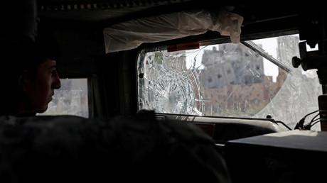 Ein Fahrer steuert sein Fahrzeug vorbei an zerstörten Gebäuden, Rakka, Syrien, Oktober 2017.