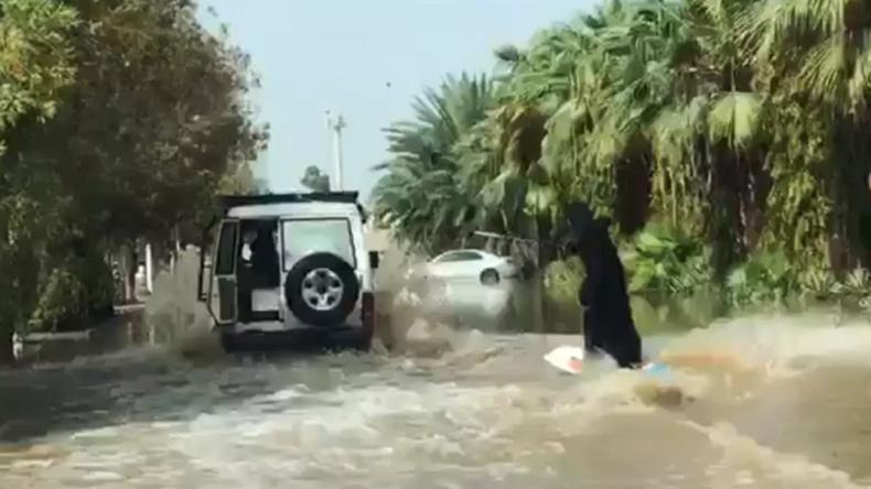 Frau im Nikab demonstriert ihr Surf-Talent in einer überfluteten Straße in Saudi-Arabien