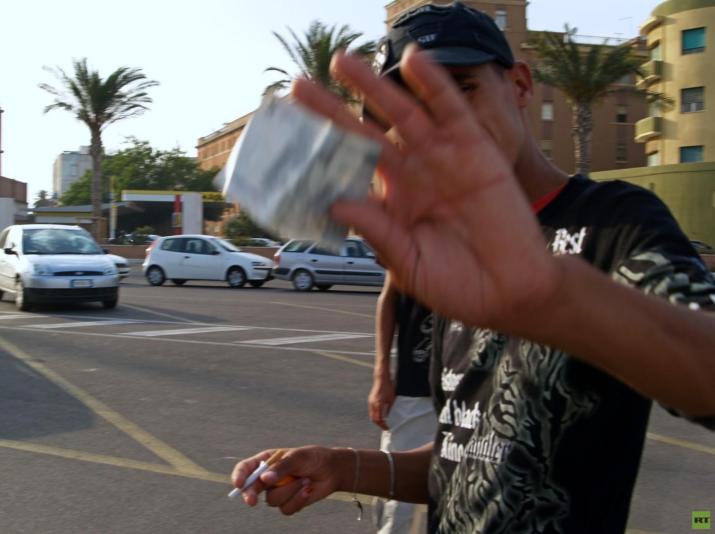 Die Harragas verbringen einige Tage in der Nähe des Hafens von Cagliari und versuchen genug Geld für eine weiterfahrt nach Italien zu sammeln. Sie betteln, oder bitten Wohltätigkeitsorganisationen um die Hilfe.
