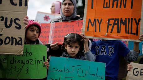 Flüchtlinge protestieren vor dem griechischen Parlament, ein Mädchen hält ein Schild hoch: