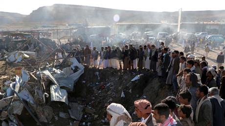 Menschen versammeln sich um einen Krater nach einem Luftschlag der saudischen Luftwaffe in Saada.