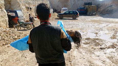 Syrien, Chan Scheichun, 4. April 2017: Ein Mann trägt ein Kind in seinen Armen, das Opfer des Giftgaseinsatzes wurde.