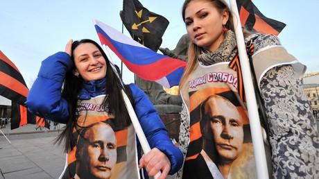 Patriotismus und Befreiung, Trikolor und St.Georgsband am Ort der Revolution: Die Teilnehmerinnen einer Kundgebung zur Unterstützung des Volksaufstandes in der Ukraine vor dem Denkmal für