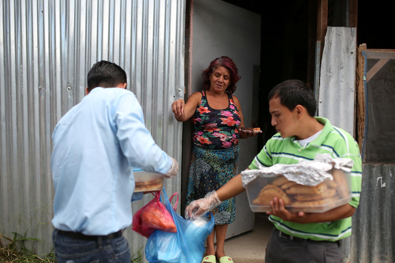 """Roberto Renderos (links) and Joseph Ramirez, Mitglieder der """"Huellas de Esperanza"""" (Spuren der Hoffnung), verkaufen Brot in San Salvador, El Salvador, 15. Dezember 2017."""