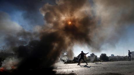 Ein palästinensischer Demonstrant benutzt eine Schleuder, um Steine gegen israelische Truppen zu werfen.