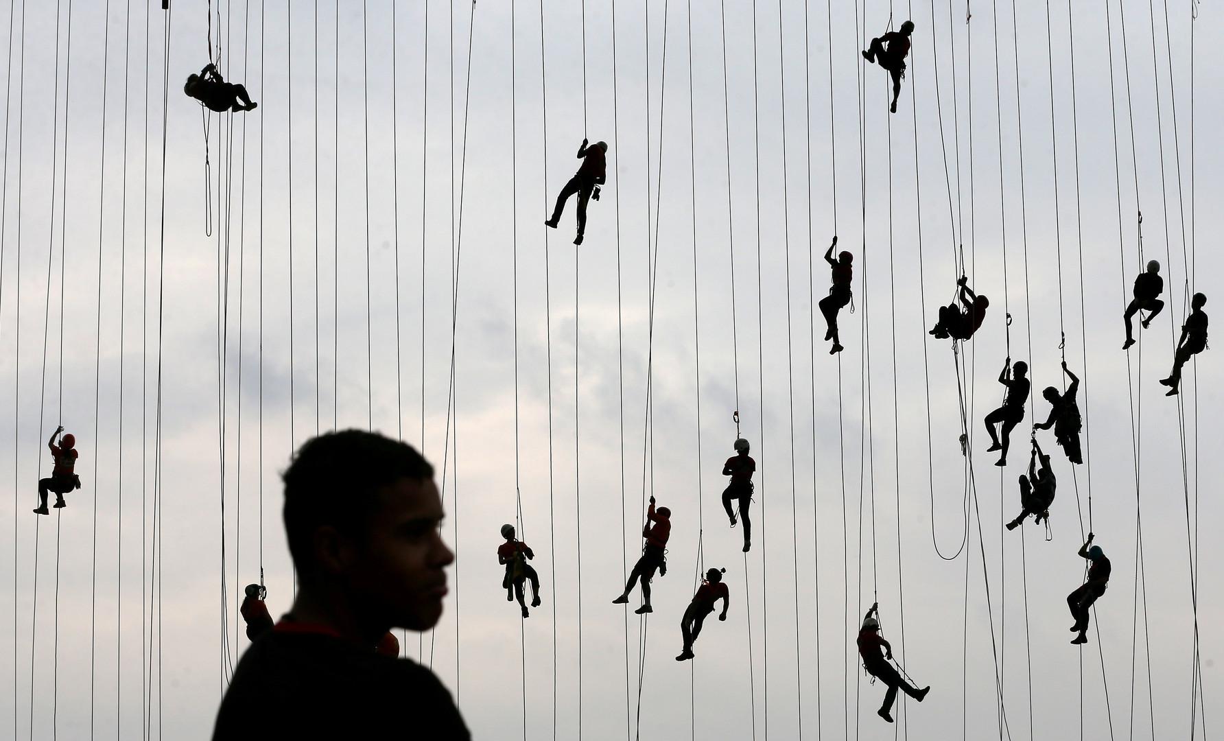 Menschen klettern Seile hoch, nachdem sie eine 30 Meter hohe Brücke in Hortolandia heruntergesprungen sind. 245 Menschen versuchten einen Weltrekord aufzustellen, in dem sie an Seile gebunden, gemeinsam von einer Brücke springen, Brasilien, 22. Oktober 2017.