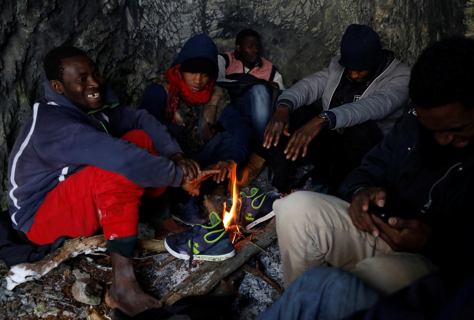 Kamarra (28 Jahre alt) Links im Bild aus Guinea, wärmt sich mit einer Gruppe von Flüchtlingen am Lagerfeuer, Nahe der Stadt Nevache, Frankreich, 21. Dezember 2017.