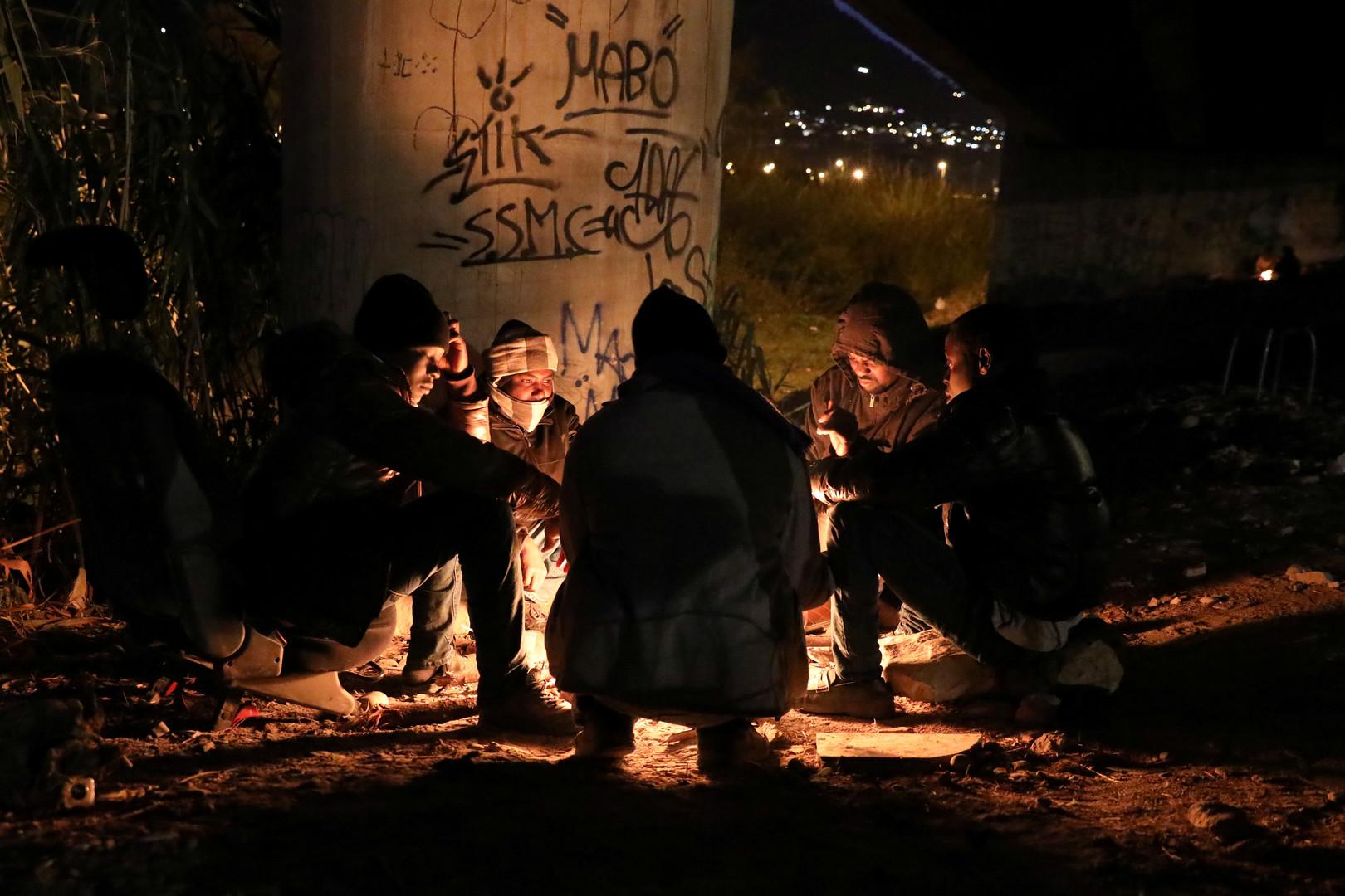 Eine Flüchtlingsgruppe, von denen die meisten aus dem Sudan stammen, wärmen sich an einem Feuer, bevor sie sich auf den Weg nach Frankreich machen, Ventimiglia, Italien, 3. Dezember 2017.