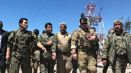 Ein US-Militärkommandant (zweiter von rechts) geht mit kurdischen Kämpfern der Volksverteidigungseinheiten (YPG) am Hauptquartier der YPG bei Malikiya in Syrien, am 25. April 2017 spazieren.