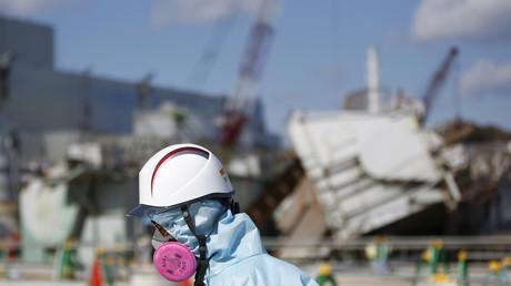 Ein Mitarbeiter von Tokyo Electric Power Co. (TEPCO), der einen Schutzanzug und eine Maske trägt, befindet sich vor dem Reaktorgebäude Nr. 1 des von einem Tsunami zerstörten Kernkraftwerks Fukushima Daiichi in der japanischen Stadt Okumain der Präfektur Fukushima (10. Februar 2016).
