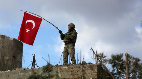 Ein türkischer Soldat schwenkt die Flagge seines Landes auf dem Berg Barsaya, nordöstlich der syrischen Stadt Afrin.