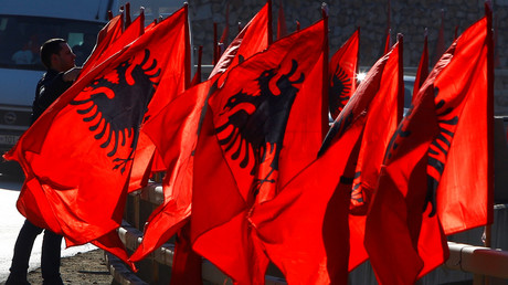 Ein Mann richtet albanische Flaggen im Vorfeld der Feierlichkeiten des 10-jährigen Unabhängigkeitstages in Kacanik, Kosovo.