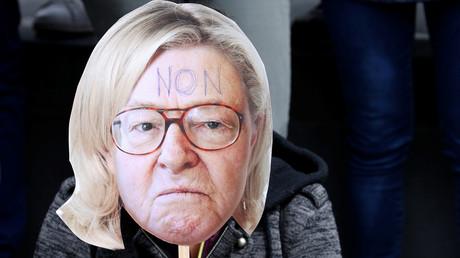 Ein Demonstrant trägt eine Maske, die das Gesicht von Jean-Marie Le Pen, dem Gründer des Front National, mit den Haaren seiner Tochter Marine Le Pen, Kandidatin der Partei für die Präsidentschaftswahlen 2017, zeigt.
