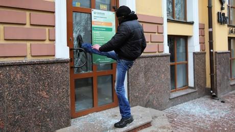 Ein Randalierer schlägt die Tür der Sberbank am 18. Februar ein.