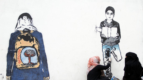 Eine jemenitische Künstlerin arbeitet an einem Wandgemälde