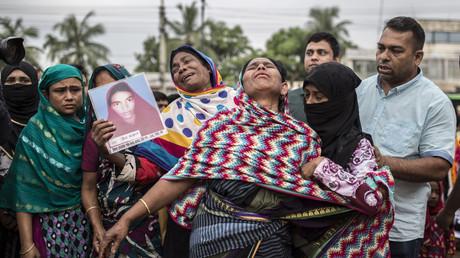 Symbolbild Angehörige von Opfern vor der Baustelle Rana Plaza (Bangladesch), wo durch unsichere Arbeitsbedingungen 1.135 Menschen starben und 2.500 verletzt wurden. Derartige Desaster sollen durch Verankerung von Menschenrechten entlang der gesamten Lieferkette von Unternehmen verhindert werden.