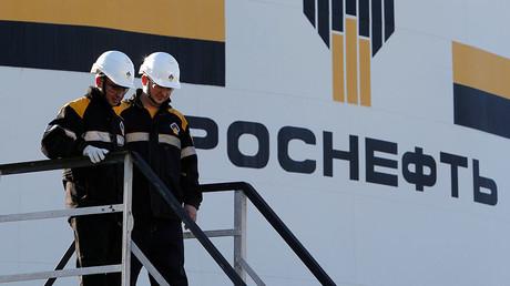 Arbeiter neben dem Logo der russischen Ölfirma Rosneft