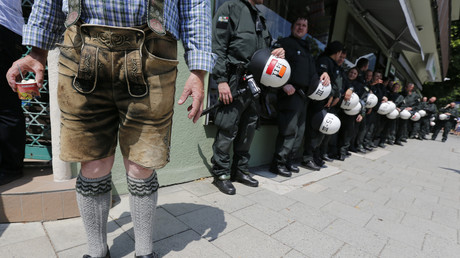 Mann in Lederhosen neben Polizisten während G7-Demonstrationen, 6. Juni 2015.