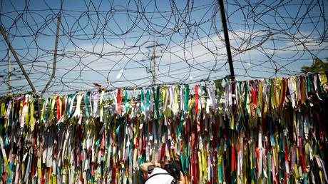 Eine Frau versucht einen Blick durch den Grenzzaun in Richtung Nordkorea zu erhaschen. Dieser ist mit Bändern dekoriert, die symbolisieren, wie die Menschen auf Wiedervereinigung hoffen, Paju, Südkorea, 15. September 2017.