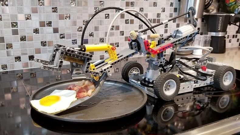 LEGO-Koch bereitet Standard-Frühstück aus Spiegelei und Bacon zu