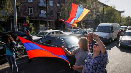 Armenische Oppositionsanhänger schwenken Nationalflaggen am Mittwochmorgen auf einer blockierten Straße in der Hauptstadt Jerewan.  Der Anführer der Protestbewegung, Nikol Paschinjan, rief zu einer landesweiten Kampagne des zivilen Ungehorsams am 2. Mai auf.