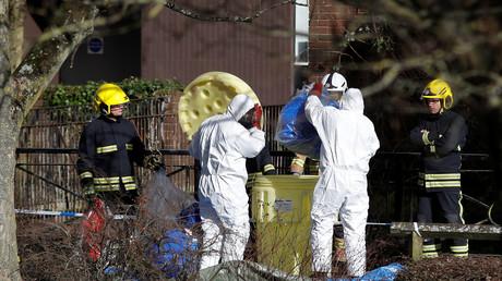 Beamte packen Schutzanzüge weg, die vorher ihre Kollegen benutzt hatten, um ein forensisches Zelt über die Parkbank aufzustellen, auf der Sergej Skripal und seine Tochter Julia Anfang März im Zentrum von Salisbury in Großbritannien bewusstlos gefunden wurden.