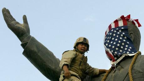 Ein US-Marine bedeckt das Gesicht einer Statue des früheren irakischen Präsidenten Saddam Hussein in Bagdad mit einer US-Flagge.