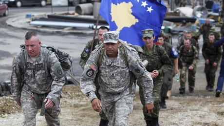 Zwei US-Soldaten schreiten vor einer Kosovo-Nationalflagge, die von Mitgliedern der Kosovo Security Force (KSF) während eines Marsches nahe der Stadt Vushtri im Norden Kosovos getragen wird, 17. Oktober 2015.