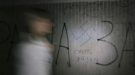 Eine Frau geht an einem Hakenkreuz und der Inschrift