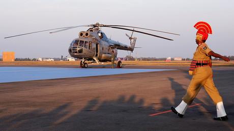 Ein indischer paramilitärischer Soldat marschiert zu einem MI-8-Hubschrauber der indischen Luftwaffe auf dem Yelahanka-Luftwaffenstützpunkt in Bengaluru, Indien.