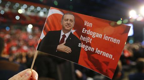 Ein Mann hält eine Fahne, die den türkischen Präsidenten Recep Tayyip Erdoğan zeigt, während der Rede des türkischen Premierministers Binali Yildirim in Oberhausen zur Unterstützung des türkischen Verfassungsreferendums am 16. April 2017, Deutschland am 18. Februar 2017.