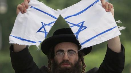 Ein anti-zionistischer orthodoxer Jude protestiert mit einer zerrissenen Israel-Flagge gegen den Staat Israel, New York.