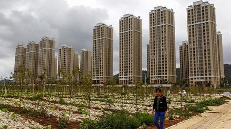 Ein Bauer spaziert an einem Gemüsefeld neben vielfach noch leerstehenden Wohngebäuden in Chenggong vorbei, einem neuen Stadtteil von Kunming, Provinz Yunnan, Volksrepublik China. (Symbolbild)