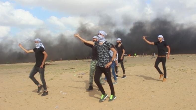 Steinewerfer-Choreografie? Protestler performen Tanz vor rauchendem Grenzzaun zu Israel