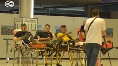 Ukrainische Soldaten begrüßen sich mit fragwürdigen Gesten auf dem Kiewer-Flughafen vor dem Transport in Bundeswehrkrankenhäuser nach Deutschland. - Quelle: Screenshot DW