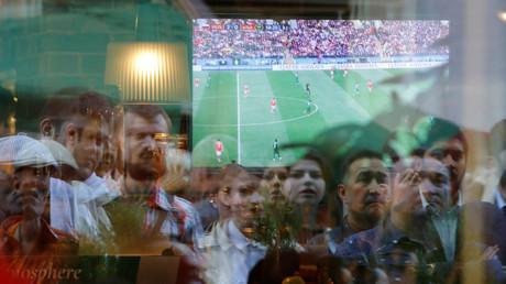 Ihre Gesichter spiegeln sich in der Scheibe eines Restaurants: Rund um den Erdball verfolgen Fans (wie hier in Moskau) die Spiele der Fußball-WM in Russland. Auch in der Ukraine sind die Einschaltquoten hoch.