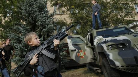 Archivbild: Ein Junge hält ein Kalaschnikow-Sturmgewehr hoch, während er mit ukrainischen Soldaten in Soledar, Ostukraine, am 27. September 2014, interagiert. Die Kinder wurden von den Soldaten beim Umgang mit Waffen unterwiesen.