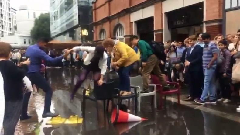 Britischer Sommer ist zurück: Londoner bauen Brücke aus Stühlen über eine Pfütze