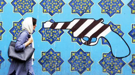 Eine Iranerin geht an einem von der Führung in Auftrag gegebenen Wandgemälde auf der Außenmauer der ehemaligen US-Botschaft in der iranischen Hauptstadt Teheran vorbei.