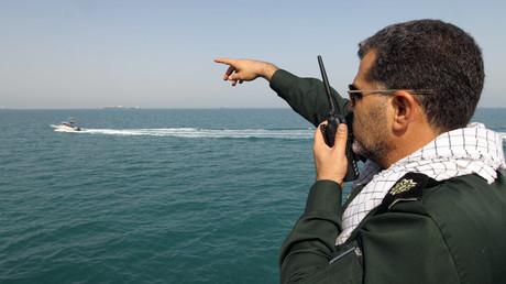Ein iranischer Revolutionsgardist gibt Anweisungen für Schnellboote auf dem Wasser während einer Zeremonie zum Gedenken an den 24. Jahrestag des Absturzes des Iran Air Fluges 655 durch die US Navy im Hafen von Bandar Abbas am 2. Juli 2012.