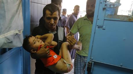 Ein Vater trägt nach einem israelischen Luftangriff seinen verwundeten Sohn ins al-Shifa-Krankenhaus in Gaza.