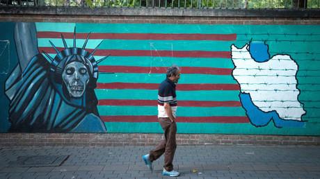 Ein Passant passiert eine Mauer mit antiamerikanischer Symbolik in Teheran, August 2018
