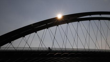 Ein Radfahrer überquert eine Mainbrücke in Frankfurt am Main.