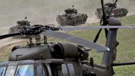 Schützenpanzer der Bundeswehr fahren an einem US-Hubschrauber UH-60 Black Hawk während der Abschlusszeremonie der NATO-geführten militärischen Übungen