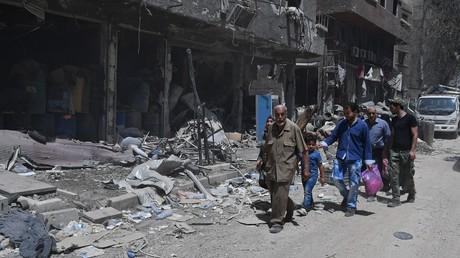 Menschen vor den zerstörten Gebäuden in Yarmouk in Syrien, das von den IS-Kämpfern befreit wurde. Immer mehr Flüchtlinge kehren in ihre Heimatstädte zurück.